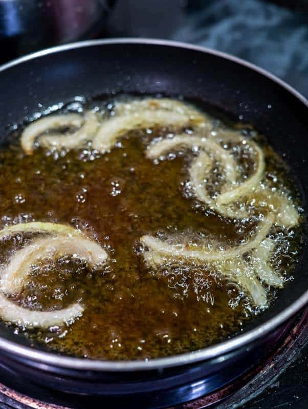 Bubbling onions floating in a shallow layer of oil in a pan