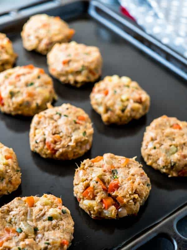 A black baking tray with uncooked, formed canned tuna fish cakes.