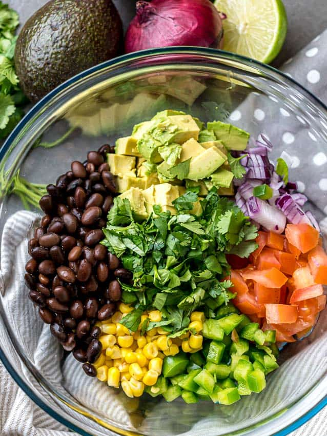 top shot of a clear mixing bowl with unmixed ingredients for chopped mexican salad.