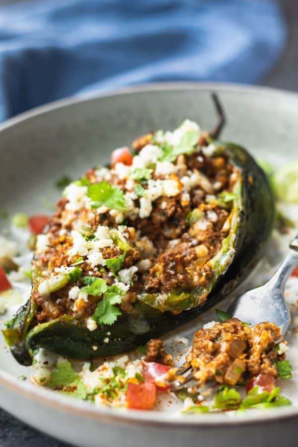 Stuffed poblano peppers with Mexican ground beef topped with fresh herbs on a light gray plate.