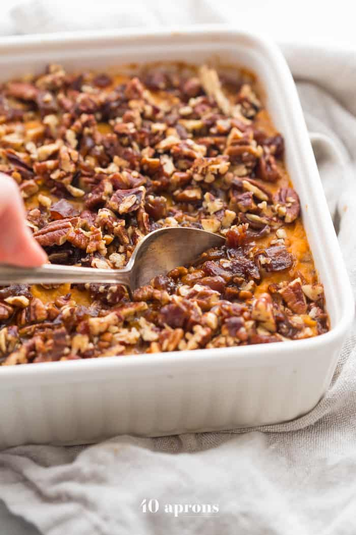 Healthy sweet potato casserole with pecans in a white dish on a white background.