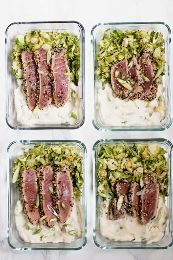 Tuna, mashed cauliflower and brussels sprouts keto meal prep recipe arranged in four glass containers on a white background.