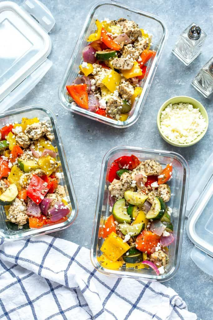 Greek chicken and vegetable mix topped with crumbled feta in three glass containers on a gray background.