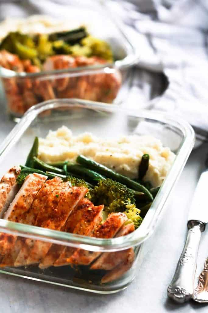 Sliced chicken, broccoli, green beans and mashed cauliflowers arranged in two glass containers on a gray background.