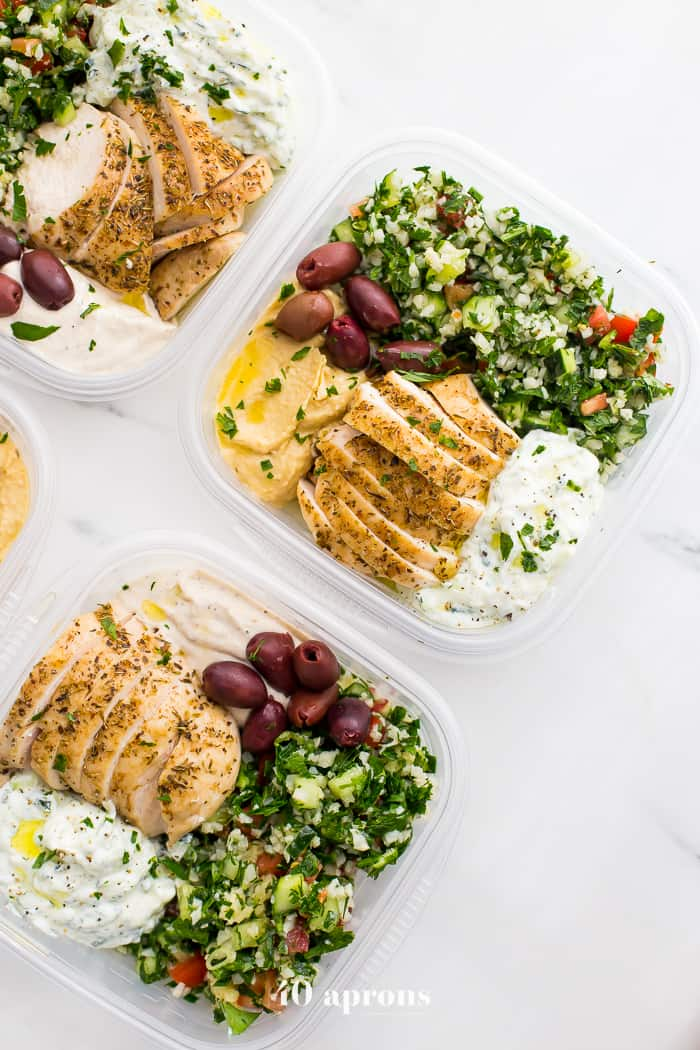 Greek keto meal prep dish in four glass containers on a white background.