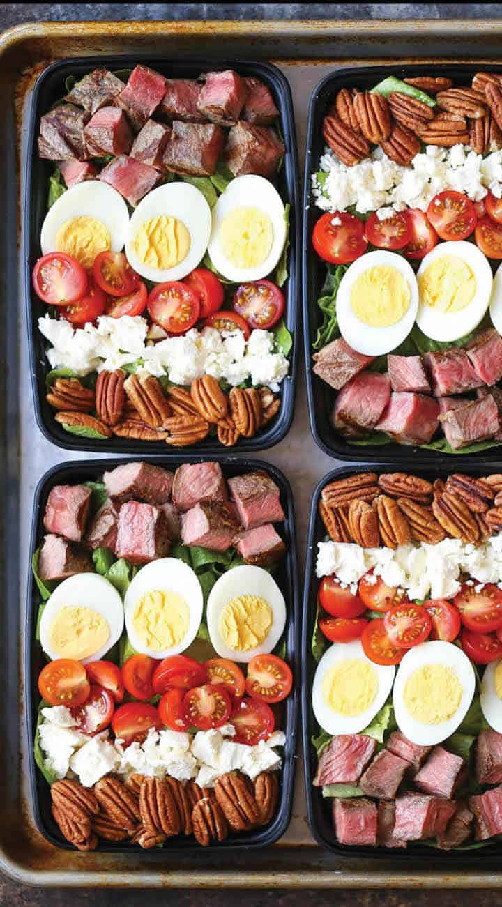 Steak cobb salad keto meal prep recipe arranged in four black containers on a sheet pan.