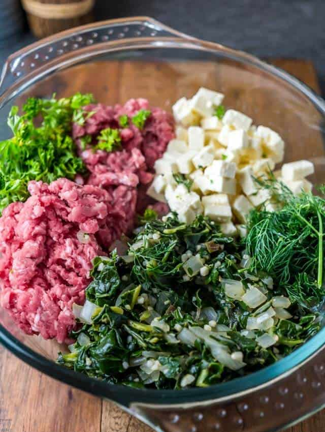 high side shot of raw ingredients for spinach and feta meatballs in a glass bowl