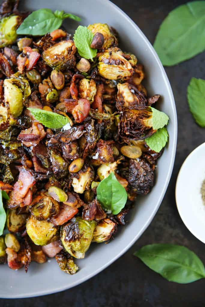 air fryer bacon brussels sprouts in a bowl garnished with fresh herbs