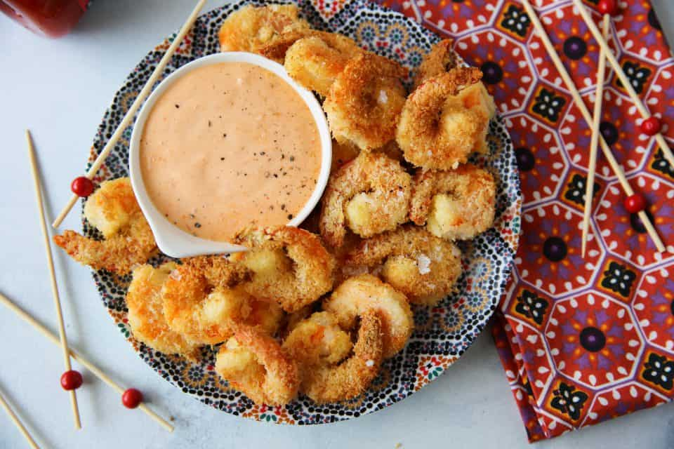 coconut shrimp with sriracha dipping sauce on a colorful plate