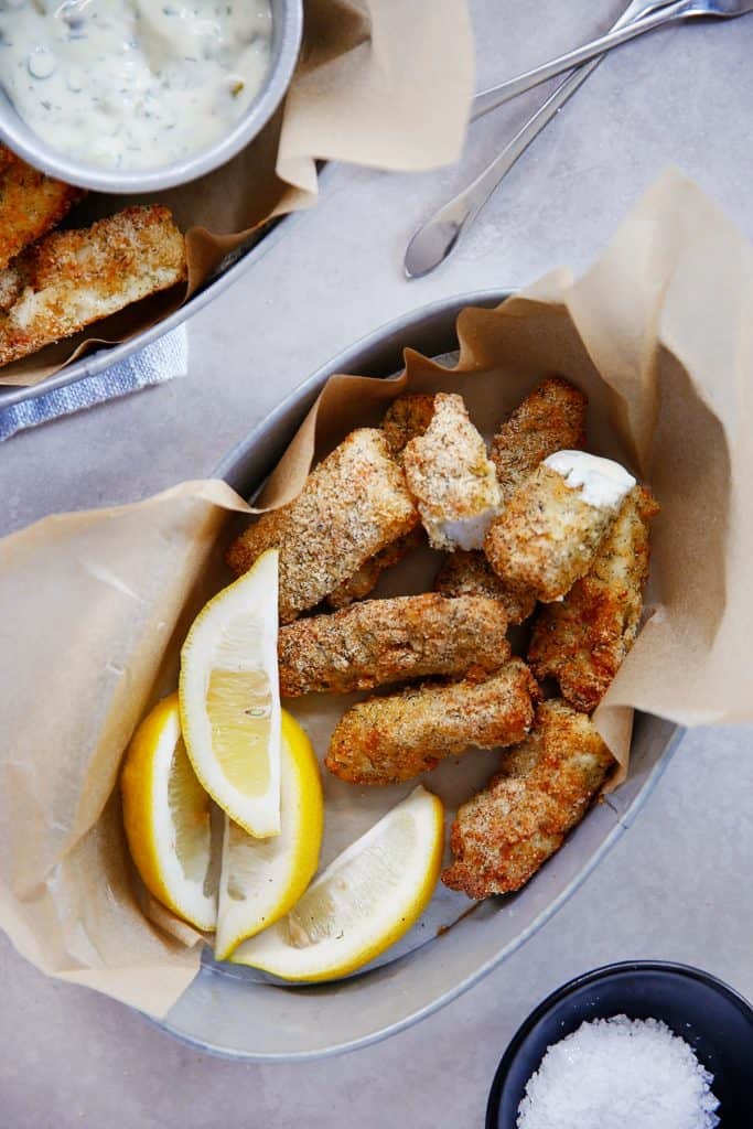 keto fish sticks in brown paper with fresh lemon wedges