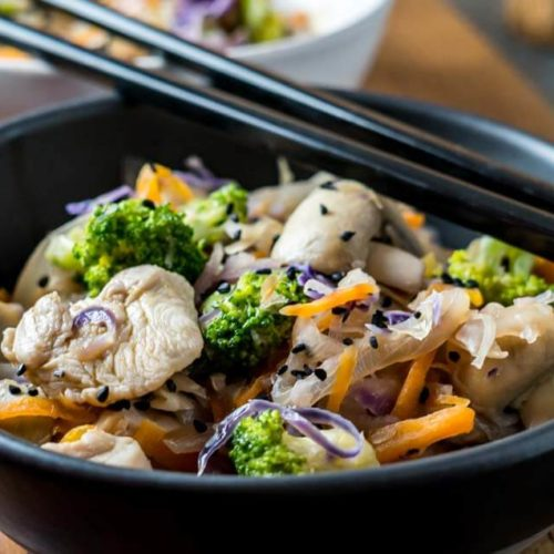 high side shot of black bowl filled with stir fried chicken and vegetables and black chopsticks