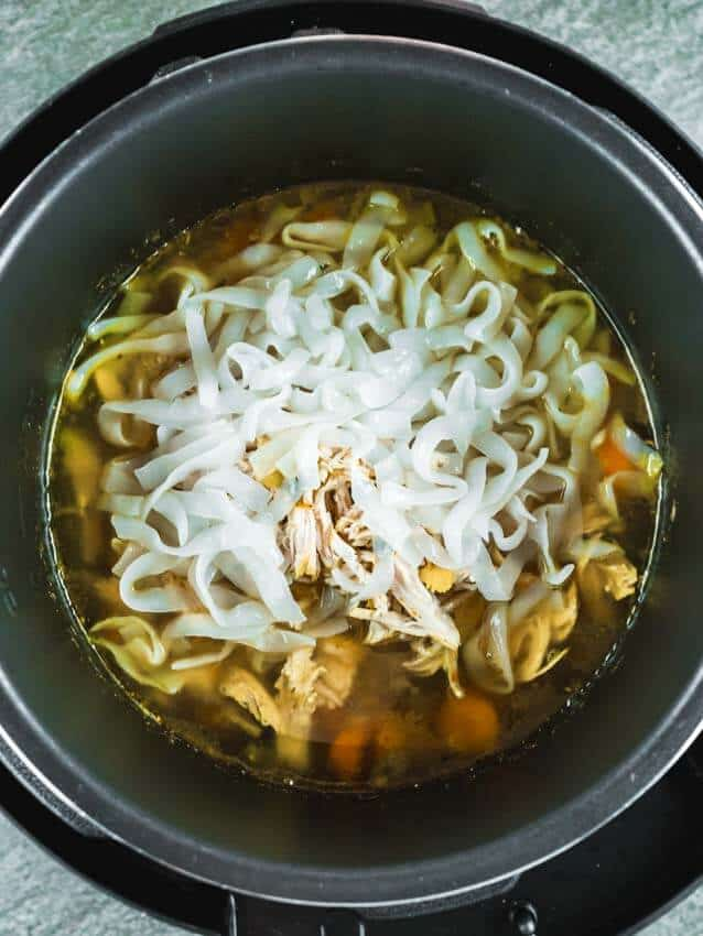 Top shot of cooked chicken noodle soup ingredients in an instant pot. Shirataki Noodles added on top.