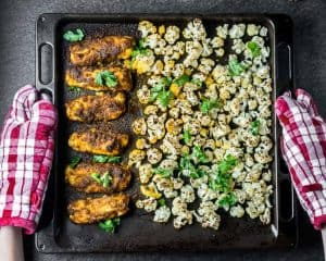 Top shot of a black sheet pan with cauliflower and tandoori fish, held by red oven mitts.
