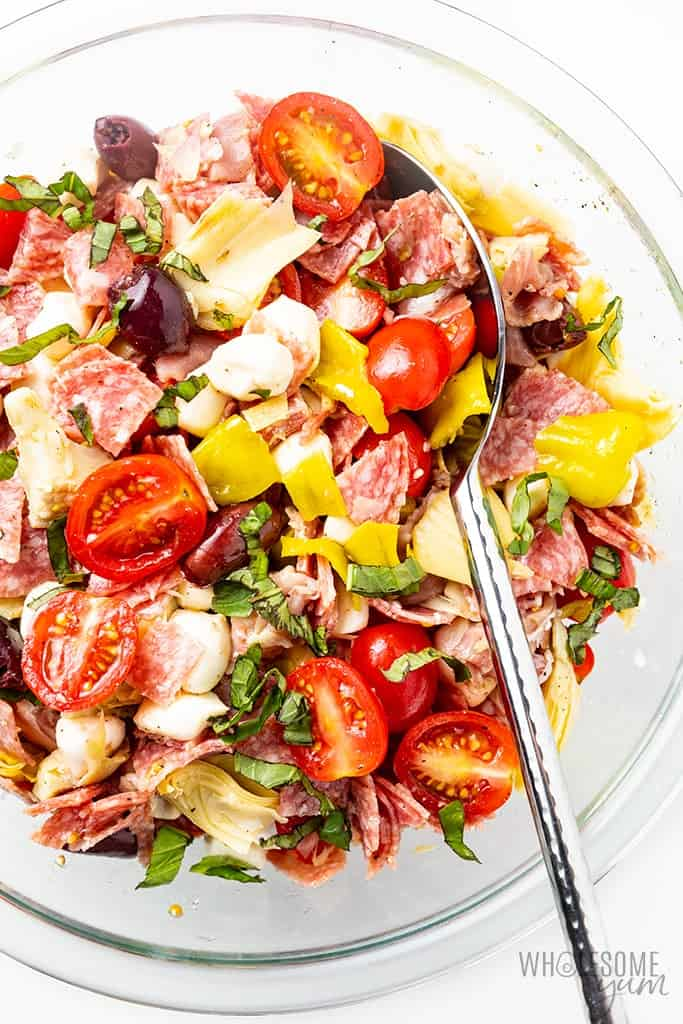 Chopped Italian Keto Antipasto Salad topped with fresh herbs in a glass bowl on a white background.