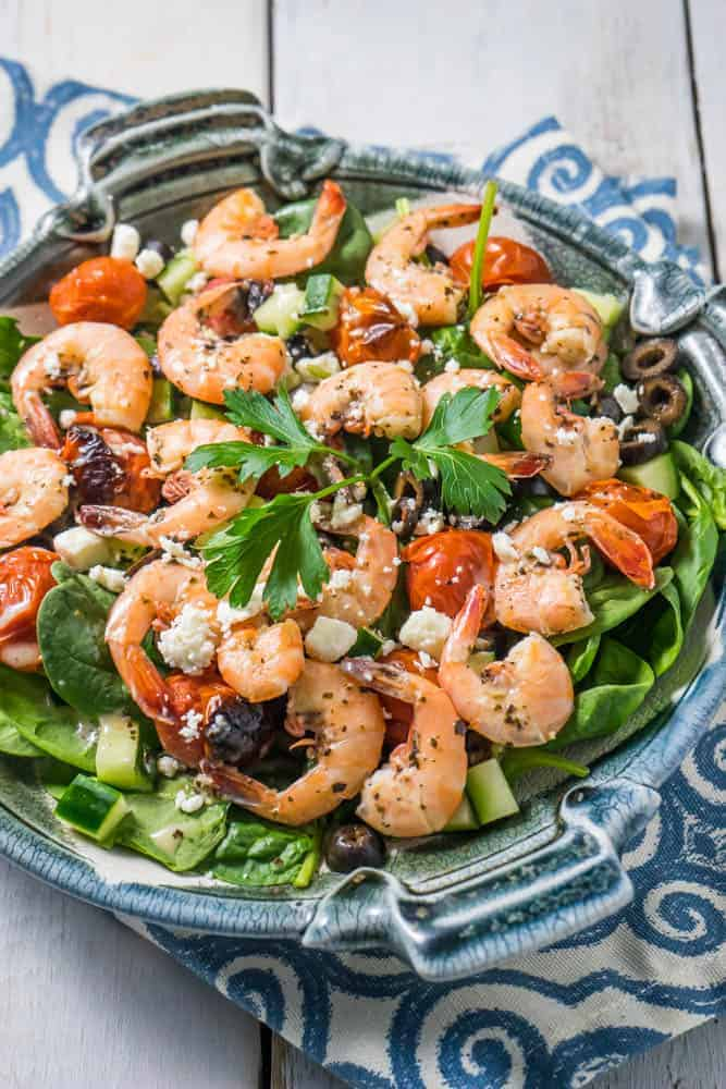 Greek Keto shrimp salad topped with fresh cilantro in a gray plate one a blue and white kitchen towel.