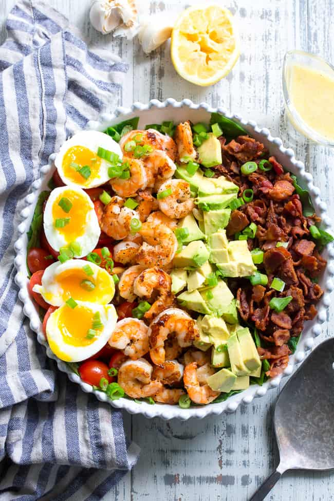 Keto cobb salad with shrimp and garlic vinaigrette topped with fresh chopped chives in a white bowl on a white background.