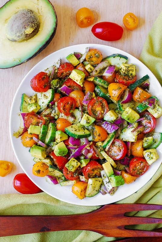 Tomato cucumber avocado salad in a white bowl surrounded by fresh chopped vegetables on a wood background.