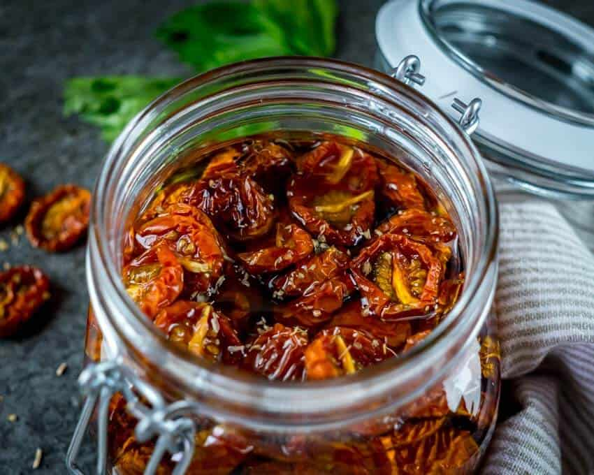 Low top shot of clear glass jar filled with sun-dried cherry tomatoes and oil with fresh herbs in the background.