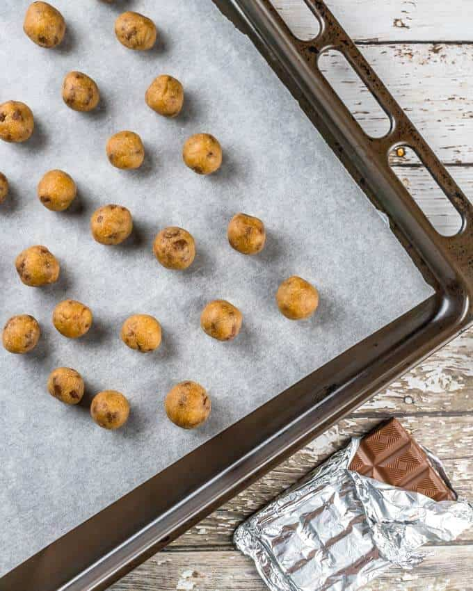 Top shot of keto cookie dough balls on baking paper on an oven tray.