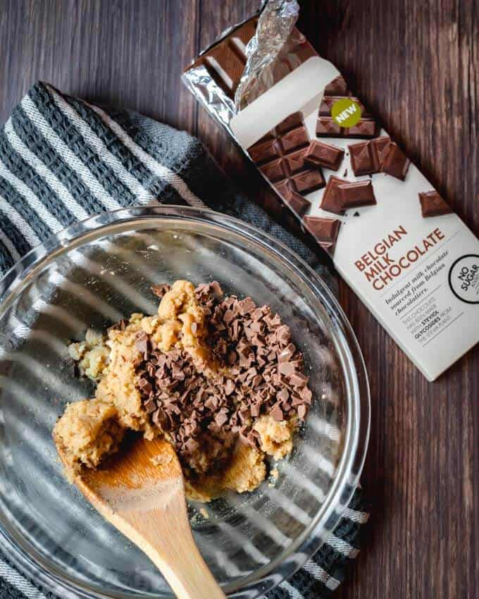 A top shot of cookie dough and chocolate bits and a wooden spoon in a clear mixing bowl, sitting on a white a grey rag on a dark wood background. Sugar Free Chocolate lays to the right.