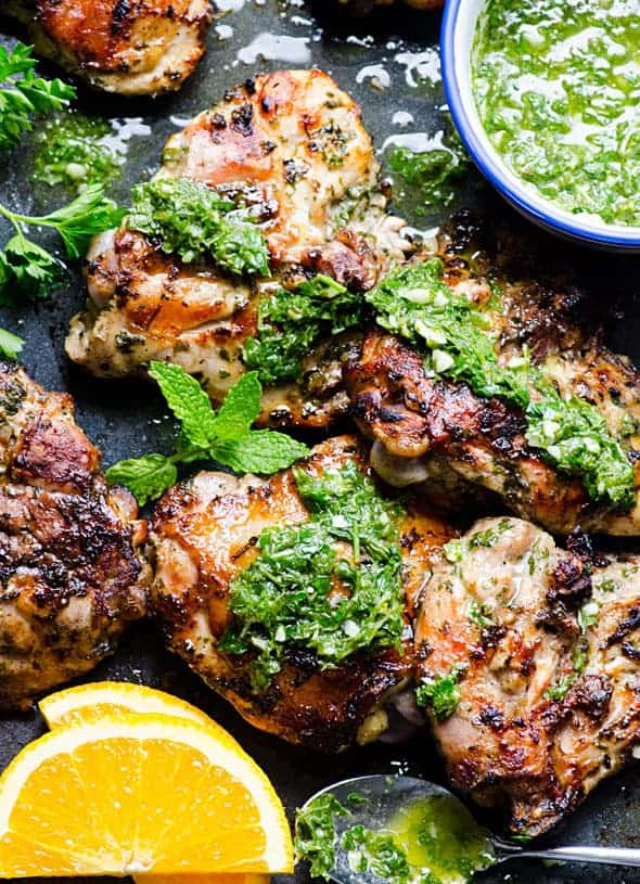 Grilled chimichurri chicken thighs topped with fresh herbs on a black serving tray.