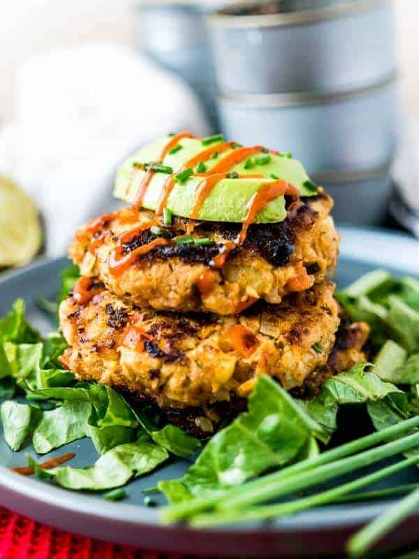 Tuna keto fish cakes topped with fresh avocado, chives, and sauce on a blue plate with leafy greens.