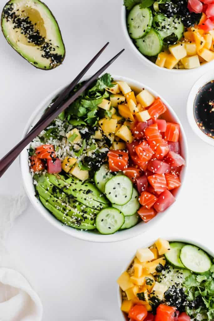 top image of keto sushi poke bowl in white bowl with chopsticks resting on the bowl