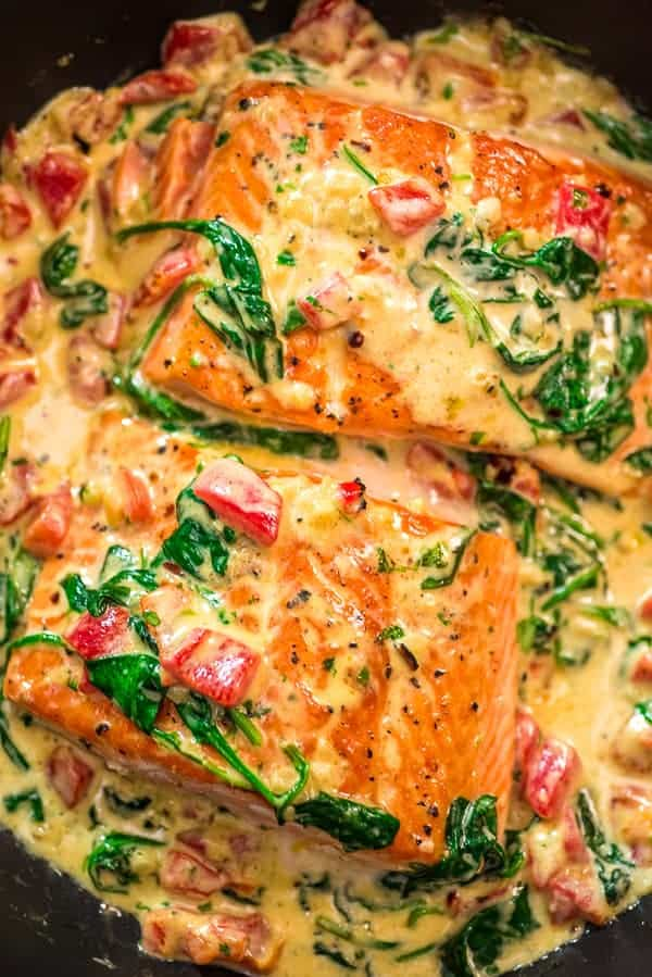 Salmon in a creamy roasted spinach and pepper sauce in a black skillet.