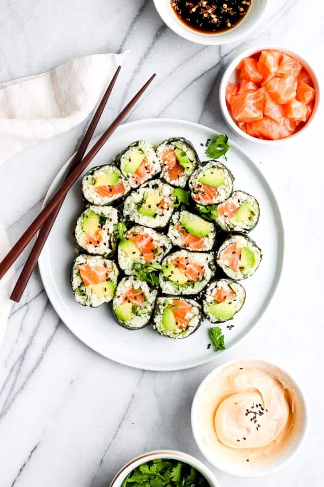 keto sushi roll with cucumber rice on a white plate, chopsticks to the side