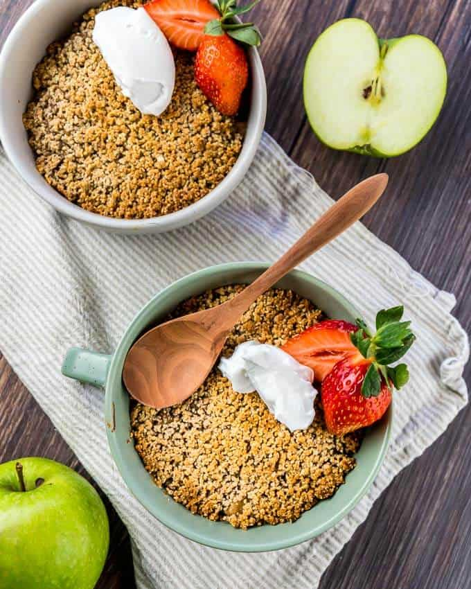 top shot of two bowls of Keto apple crumble with fresh strawberry garnish and coconut cream. on a white and grey striped dish rag. Half an apple in the right corner