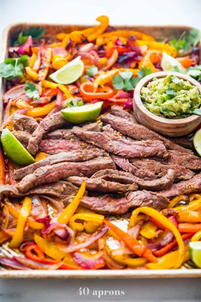 High angle side shot of steak strips, bell pepper slices, three lime wedges in a sheet pan, with a small wooden bowl filled with guacamole in the top right, on a light gray background.