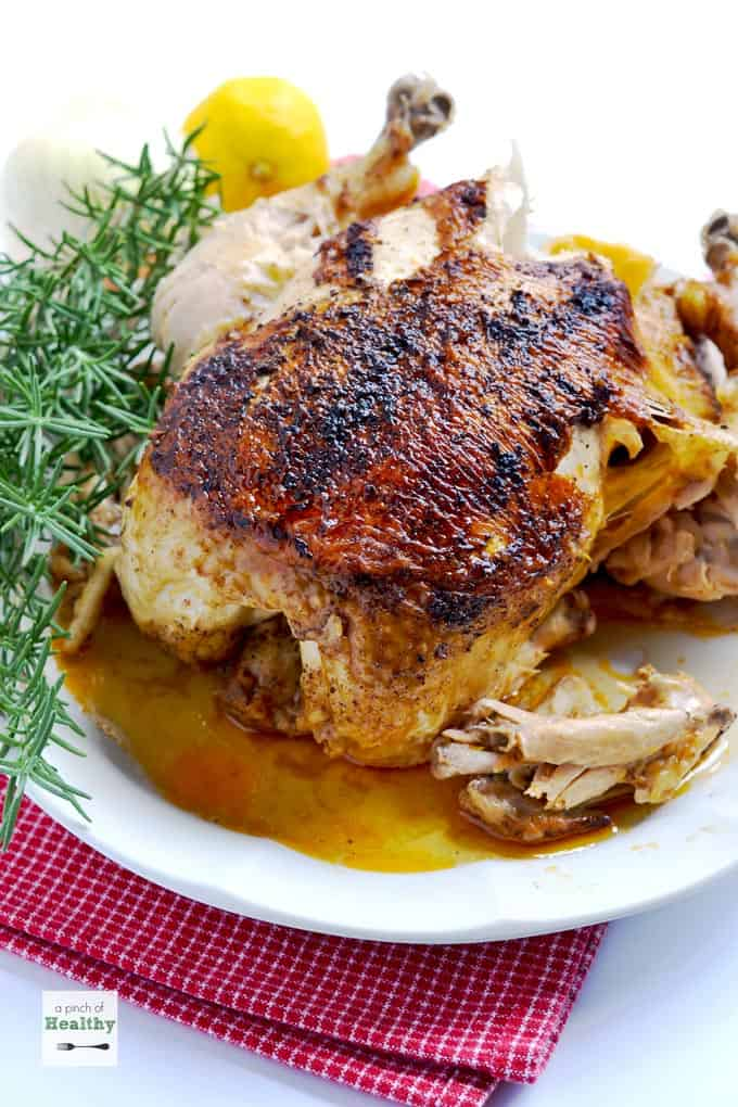 high angle side shot of whole chicken on a white plate on top of a red kitchen towel with fresh rosemary on the left side