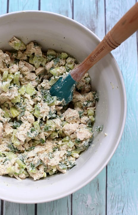 top shot of cucumber dill chicken salad in a large white bowl with a wooden spatula on a light gray wooden background