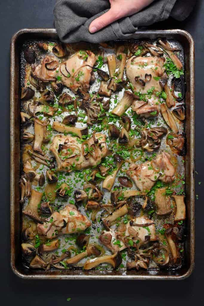 Top shot of chicken pieces surrounded by sliced mushrooms garnished with fresh herbs in a metal sheet pan, on a dark gray background.