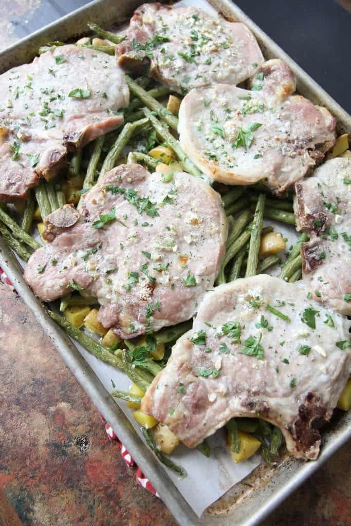 High angle side shot of six pork chops garnished with fresh herbs on a bed of green beans in a metal sheet pan, on a light brown and gray background.