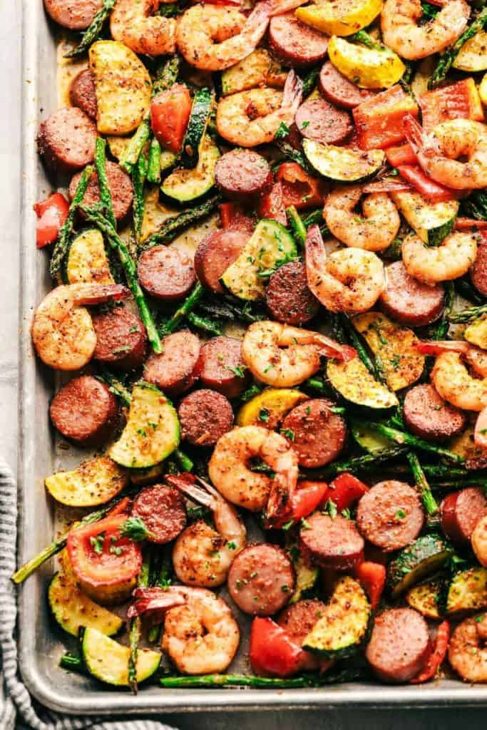 Top shot of an assortment of shrimp, sausage slices, bell pepper, asparagus in a metal sheet pan.
