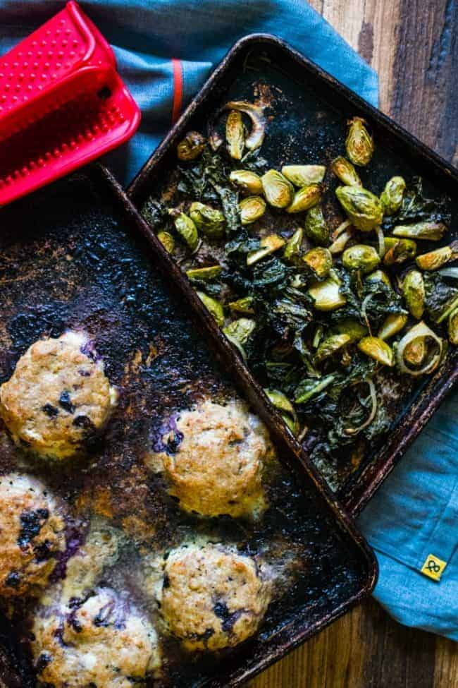 Top shot of two overlapping metal sheet pans, bottom one filled with brussels sprouts and kale, top one filled with ground turkey burgers, red oven mitt in the top left corner, on a blue and brown background.