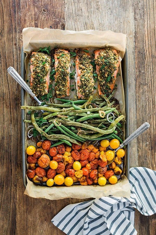 Top shot of herb crusted salmon, green beans and cherry tomatoes in a sheet pan, with a stripe kitchen towel in the bottom right corner, on a wooden background.