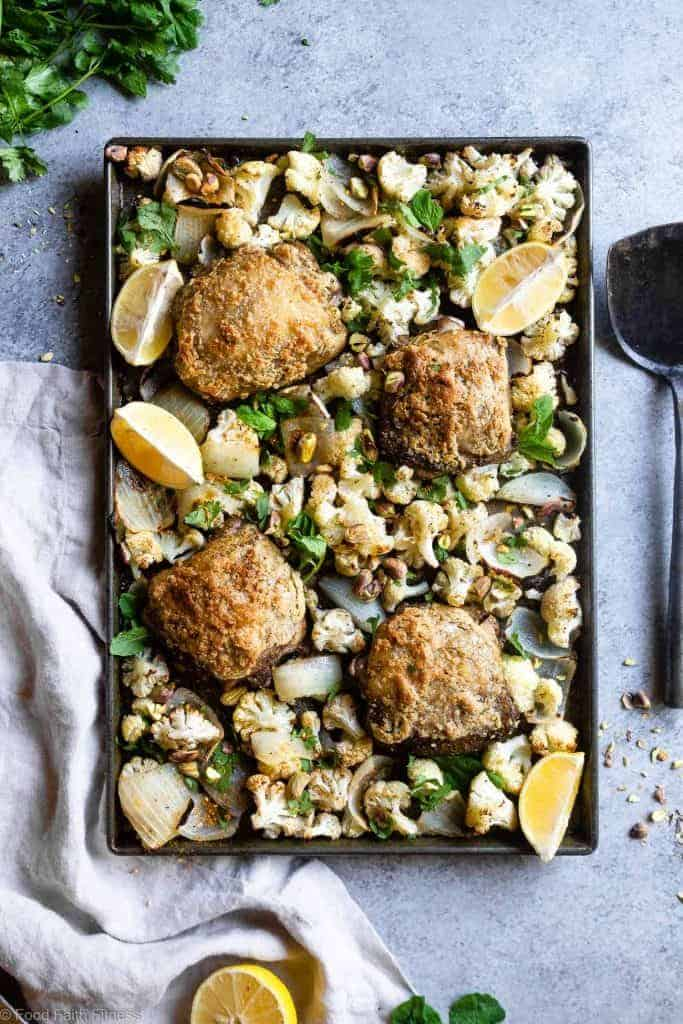 Top shot of four crusted chicken thighs surrounded by cauliflower florets, onion slices, pistachio nuts, lemon wedges in a metal sheet pan, with a white kitchen towel in the bottom left corner, on a light gray background.