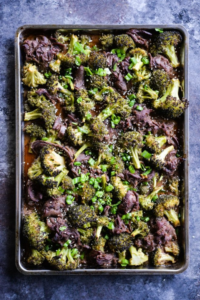 Top shot of beef slices and broccoli florets garnished with sesame seeds and chopped chives in a metal sheet pan, on a dark gray marble background.