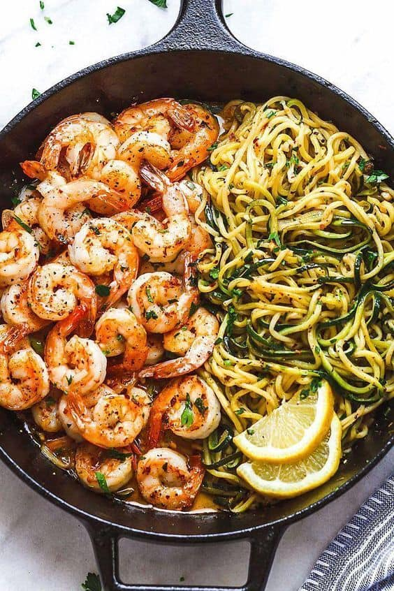 Cooked shrimp on left side and zucchini noodles to the right in a black skillet on a white background.