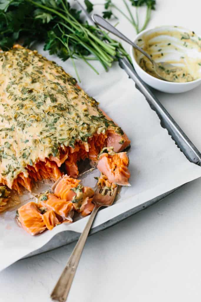 Baked Salmon topped with creamy dijon sauce on a sheet of baking paper in a tray.