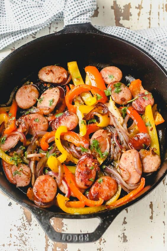 Sliced sausage and bell peppers topped with chopped fresh herbs in a black skillet on a white wooden background.