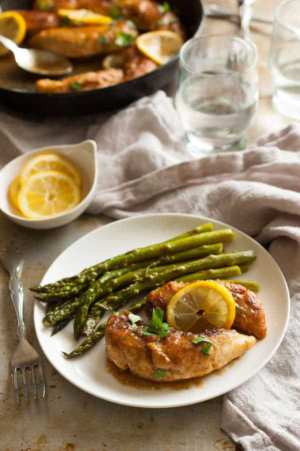 Chicken with a slice of lemon and bunch of asparagus on a white plate with a neutral background.