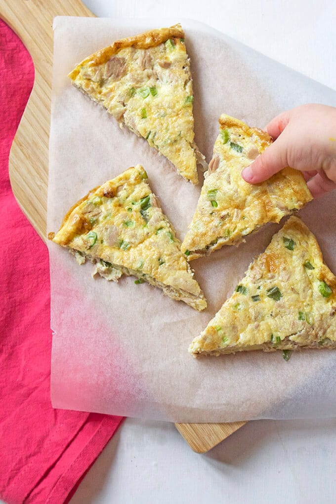 Four slices of canned tuna frittata on a wooden tray with a red background.