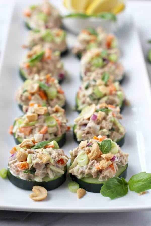Cashew tuna salad cucumber bites topped with fresh basil on a square white plate.