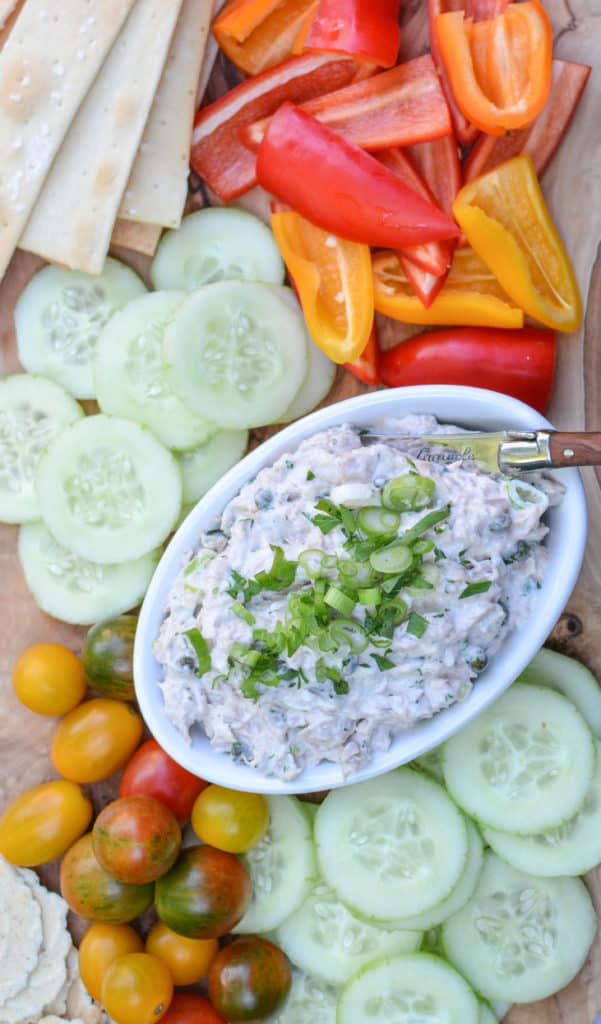 Truffle tuna dip topped with fresh herbs and spring onion in a white bowl surrounded by fresh tomatoes cucumber and peppers.