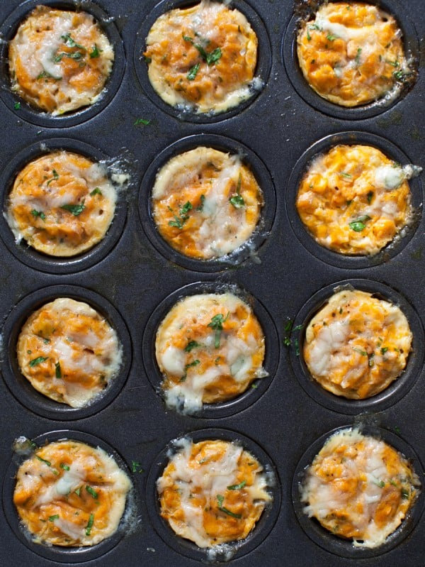 12 tuna cheddar eggs muffins topped with fresh herbs in a dark gray pan.