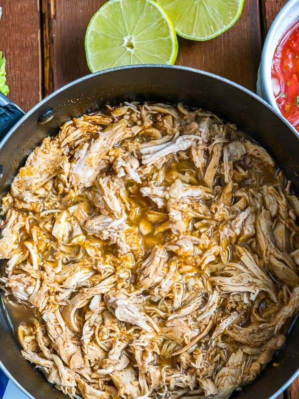 mexican shredded chicken in a pot, fresh lime visible on the side