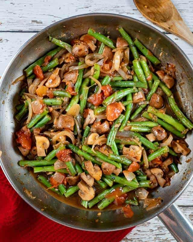 Top shot of Sauteéd Green Beans in a pan with a wooden spoon in the upper right corner.